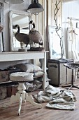 Stuffed goose and vintage pieces on console table