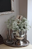 Bouquet of gypsophila in silver urn