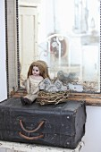 Doll next to chicken-shaped cake tin in nest on top of old suitcase