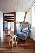 Comfortable reading chair and wooden stool below window