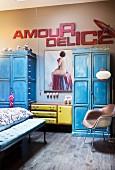 Schlafzimmer mit blauen Vintage Holzschränken, gepolstertem Retro-Sideboard unter Aktgemälde und Deko-Buchstaben an beigefarbener Wand
