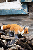 Hand-made, felted, woollen fox on firewood