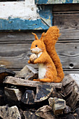 Hand-made, felted, woollen squirrel on firewood