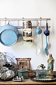 Old kitchen utensils hung from rod above Madonna figurine