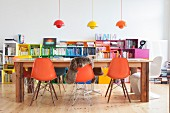 Orange shell chairs and long wooden table in front of colourful shelves