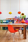 Various designer chairs and wooden table in front of colourful shelves