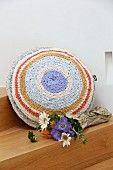 Flowers next to round cushion with crocheted cover made from T-shirt yarn