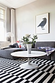 Round coffee table and grey sofa on black and white striped rug