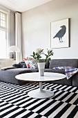 Runder Couchtisch und graues Sofa auf schwarz-weiß gestreiftem Teppich