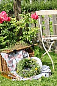 Picnic basket, blanket, enamel crockery and wreath of wildflowers in garden