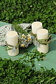 Candles decorated with chamomile flowers and checked tea towel on vintage wooden board amongst clover