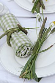 Green gingham linen napkin tied with blades of grass