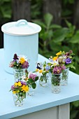 Small glass vases of colourful wildflowers on pale blue table