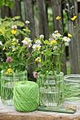 Vasendekoration mit grünem Garn und bunten Wiesenblumen