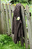 Flowers pinned to cardigan hung from vintage garden gate