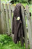 Mit Blume geschmückte Strickjacke an Vintage Gartentor gehängt