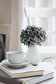 Hydrangea in white vase and teacup on book