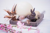 Still-life arrangement of various eggs, rabbit ornament and pink-flowering branches