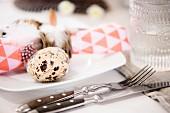 Wachtelei auf weißem Teller mit Serviette und Feder