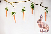 Carrots with leaves hung from branch next to printed picture of rabbit
