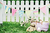 Cloth bunny and Easter eggs below pastel bunting hung on white picket fence in garden