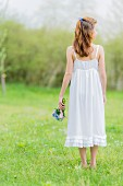Girl wearing white summer dress holding posy on lawn