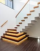 Moderne Treppe mit Holzstufen und Beleuchtung