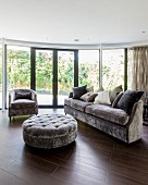 Velvet-upholstered furniture in living room with curved glass wall