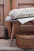Rolled, hand-woven, undyed woollen rug on wooden stool