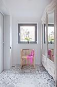 Halbrunder Stuhl vor klassischem Schrank auf gemustertem Boden