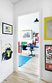 Colourful artworks in hall with view of desk in teenager's bedroom