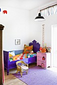 Purple-painted bed and pink bedside cabinet in child's bedroom