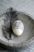 Blown egg decorated with black, printed pattern and feather in stone dish