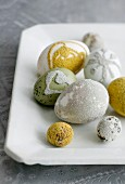 Various eggs decorated with hundreds and thousands on white porcelain plate