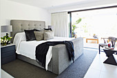 Modern upholstered bed in the bedroom in shades of gray