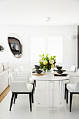 White upholstered chairs around a modern marble table