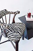 Upholstered chair with zebra pattern cover next to a modern side table