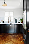 Splash guard made of marble in black kitchen with wooden floor