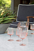 Pink relief glasses and water carafe on marble table