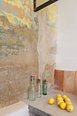 Swing-top bottle and lemons next to wall with layers of old paint