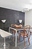 Various chairs around dining table in front of black wall