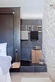 Stufe zum kleinen Bad hinter dem Bett mit schwarzer Trennwand
