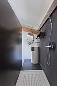 Open shower in narrow bathroom with black walls