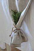 Bunch of rosemary in gathered end of ecru runner on white tablecloth