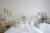 Verschnörkeltes Metallbett im weißen, nostalgischen Schlafzimmer