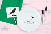 Painting a bird silhouette on a white plate