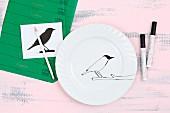 Weißer Teller wird mit einer Vogelsilhouette bemalt