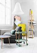 Hostess trolley, easy chair, neon-yellow chest of drawers and ladder shelving in modern, Nordic interior