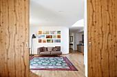 Geöffnete Holzschiebetüren, Blick in eleganten Wohnbereich mit Bildergalerie
