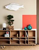 Bonsai tree and Japanese ornaments on Scandinavian shelves below accent of colour on wall and paper fish sculpture